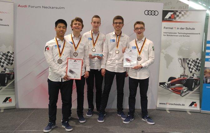 Schüler und Studenten in weißem Hemd und Medaille vor weißem Werbetafel von Audi