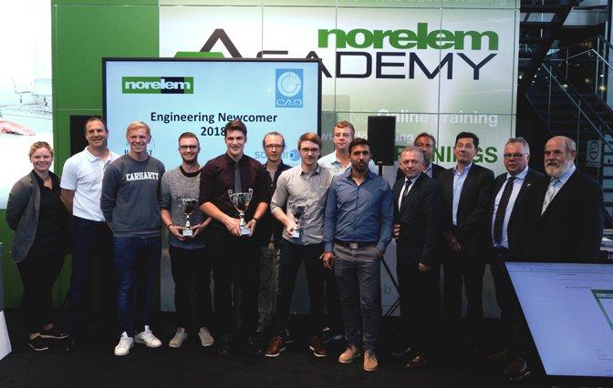 Engineering Newcomer 2018 Gewinner mit Pokal in der Hand vor einem großem Bildschirm und grün weißer Werbetafel
